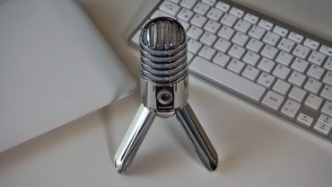 Podcasting Hardware & Software Needed-microphone, laptop and keyboard on the desk